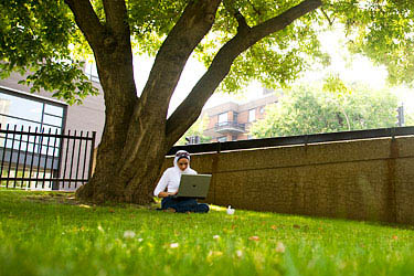 A student takes advantage of a beautiful day and the wireless Internet on campus.
