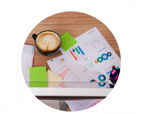 Latte on a desk beside a printed report with graphs and charts