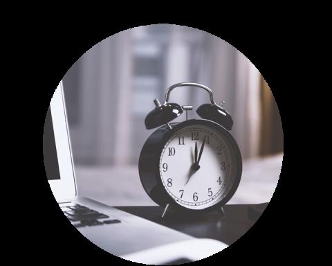 Alarm clock next to laptop