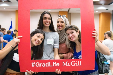 Grad students posing with a #GradLife photo prop