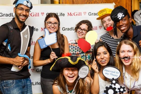 Students posing in front of a GradLife photo backdrop