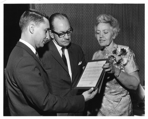 A woman holding an award, showing it to the Director of the School of Social work, and another man. Black and white photo, men in suits, woman in dress.
