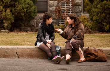 two young women, sitting on a curb having a conversation