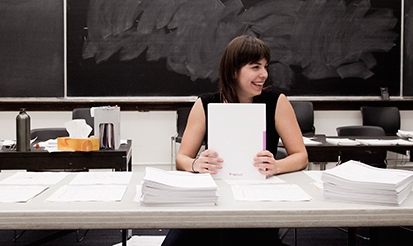 grad student surrounded by papers, still looks happy