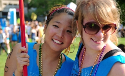 two students at FROSH week, smiling and holding signs for an event