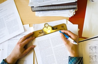 journal articles on a desk, hands hovering over top, with pen ready