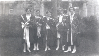 Photo of 5 women standing in front of McGIll buiding, wearing graduation gowns and holding bouquets of flowers: black and white