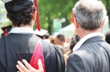 father resting hand on his graduating son's back, so proud