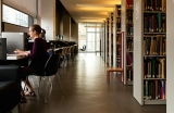 woman sitting in the library surrounded by books and her thoughts
