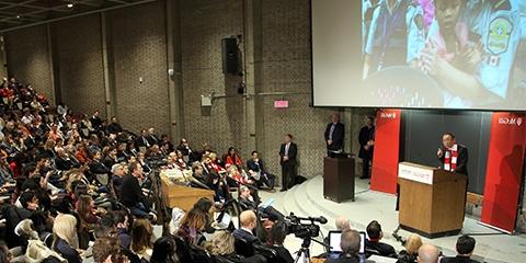 A keynote speaker addresses a large crowd