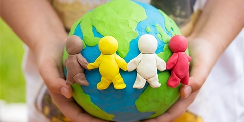 hands holding a clay globe