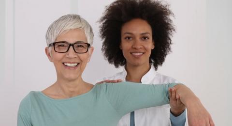 Smiling female healthcare professional evaluating a smiling senior ladies shoulder movement