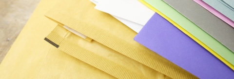 stack of yellow envelopes and coloured papers
