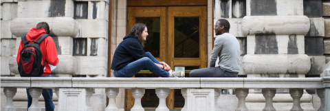 two students talking together outside a building, and a third student with their back turned