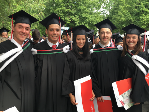 five students in caps and gowns on convocation day