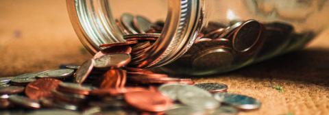 Jar of coins spilling onto carpet