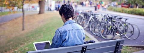 a student sitting on a bench alone on his laptop