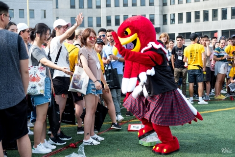 a group of students dancing with Marty, the McGill mascot