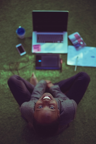 top view photo of a woman smiling up at the camera while she sits on the ground, with her MacBook, phone, and study tools lie on the ground in front of her