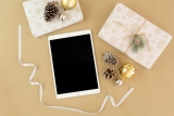 a white e-reader lies on a table surrounded by holiday gifts and decor