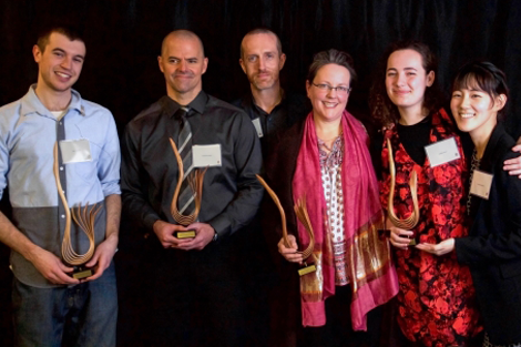 group photo of Catalyst award winners holding organically-shaped trophies in front of a black background