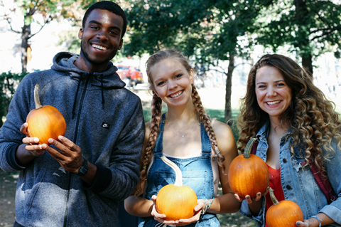 3 students holding pumpkins on McGill lower campus