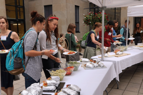 Students line up outdoors to serve sustainable meal
