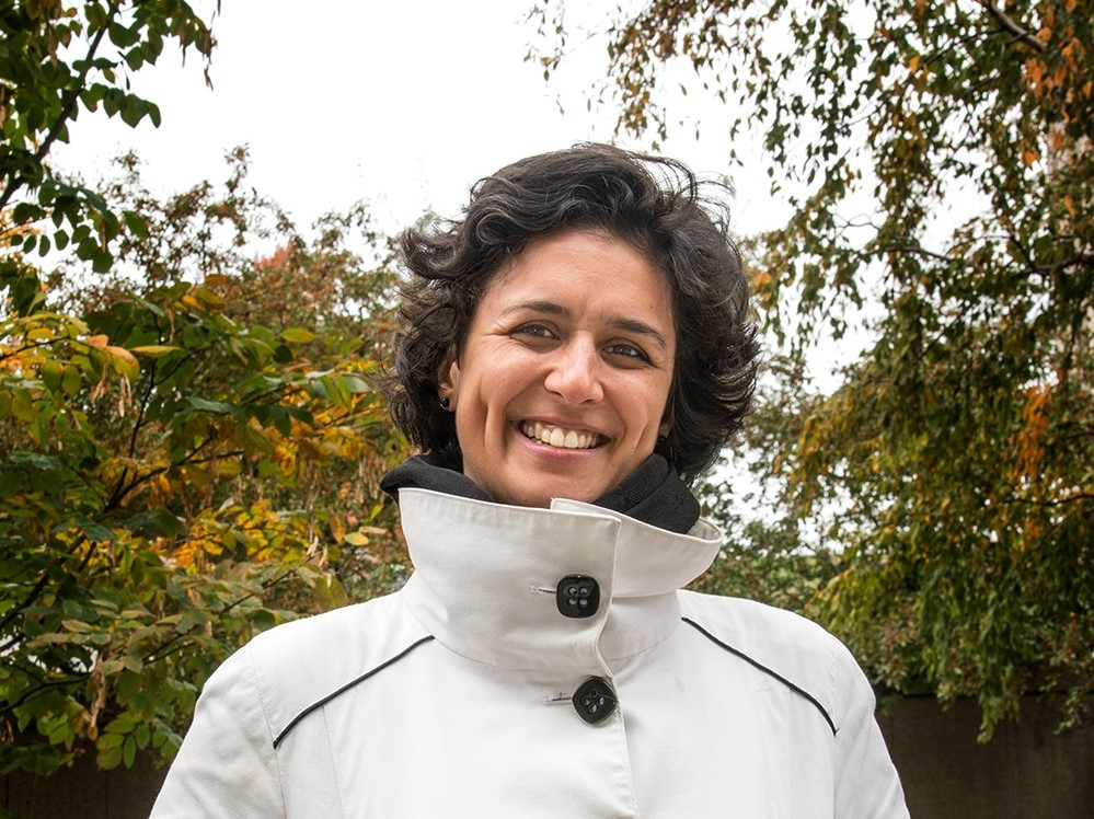 A woman in a white jacket smiles outside