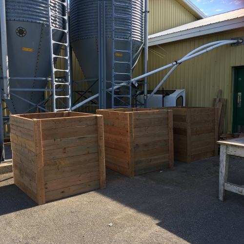 Three completed wooden compost crates outdoors