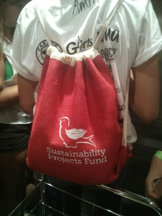 Student wearing frosh shirt with red Sustainability Projects fund bag over their back