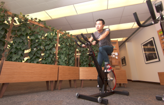 Charles Cong in McIntyre building on spin bike