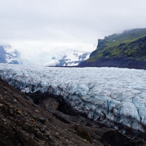 Image of artic with ice sheet and unveiled dirt and green mountain in the backgroud