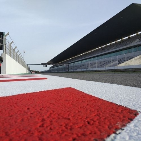 image of race track with road and stands on the sidelines