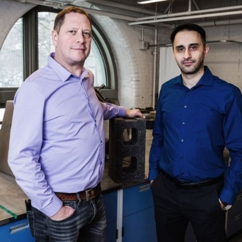 image of Mehrdad Mahoutian, and Chris Stern, with one of their cement-free, carbon-negative concrete blocks.