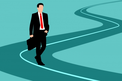 Coloured outline of a person carrying a briefcase on a winding green road