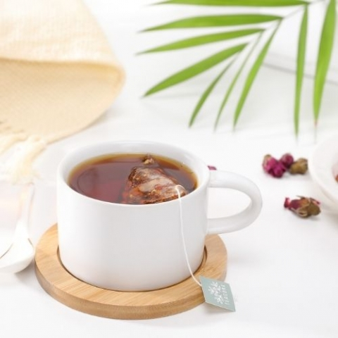 image of a cup of tea with a teabag within it and a plant leaf on the side