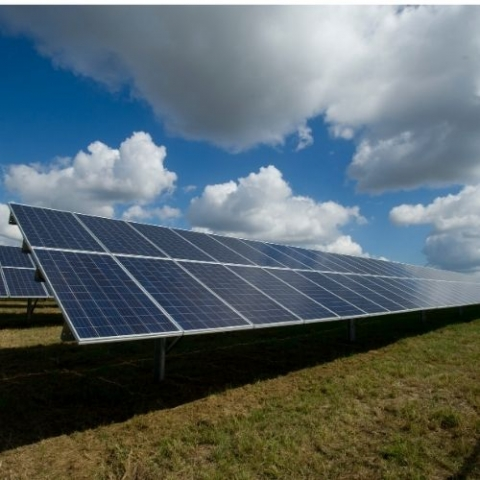 view of solar panels on grass with blue cloudy sky