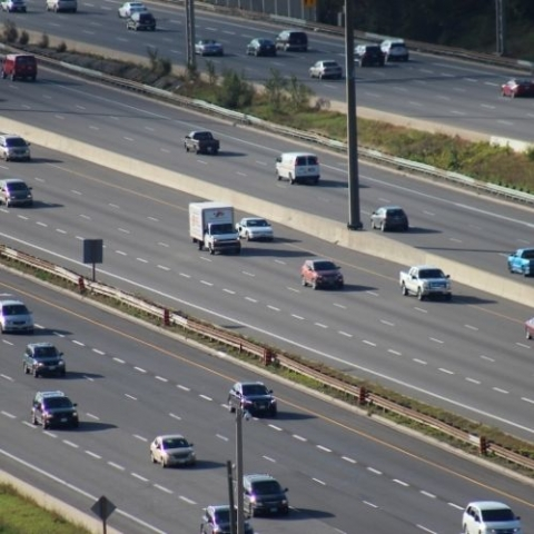 image of highway with multiple cars driving in traffic
