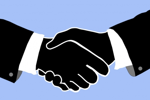 Outline of two people shaking hands on a blue background