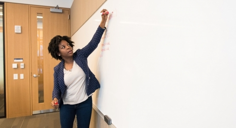 Professor writing on whiteboard