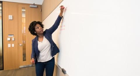 Professor writing on whiteboard