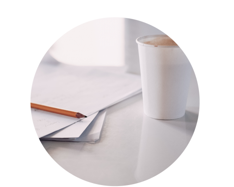 Cup of coffee next to paper and pencil