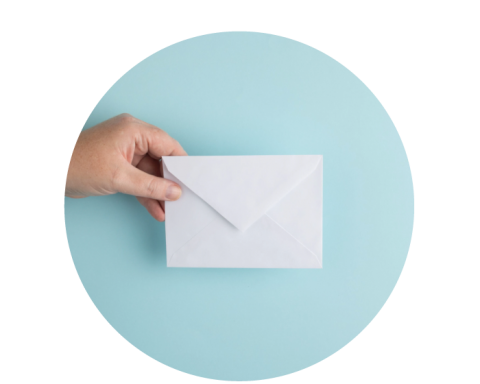 A hand holding a sealed envelope