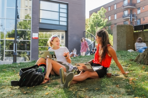 Two students on the grass at the downtown campus