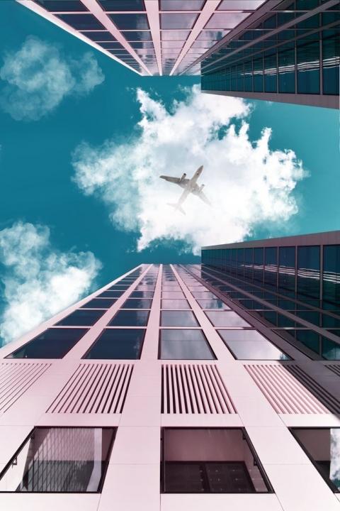 airplane flying between buildings