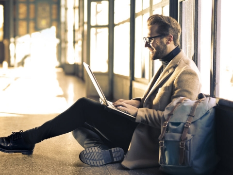 man in blazer sitting on the floor with Laptop