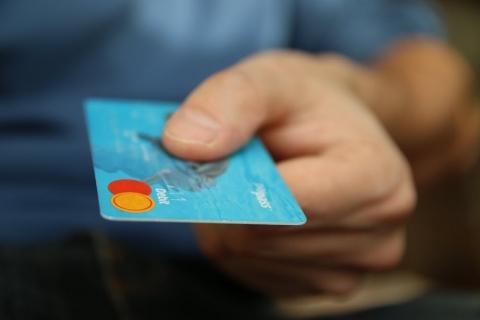 A hand holding a blue debit card