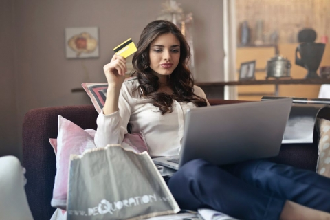 woman on couch with credit card and laptop