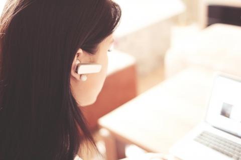 woman with earphone on computer