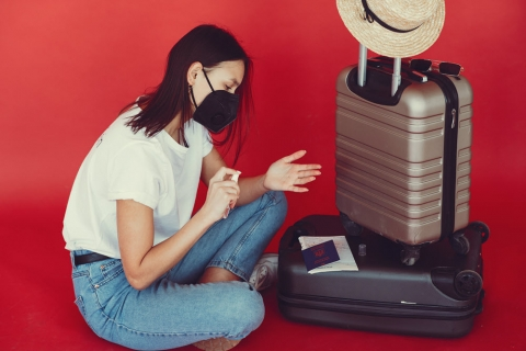 Woman sitting on the floor with packed luggage